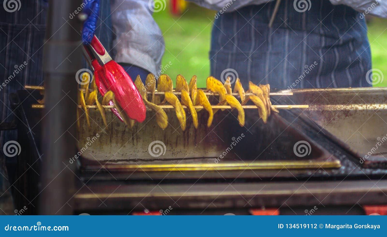Gebraden aardappels in de vorm van spiraal op houten stok De aardappels braadden tot de gouden kleur op metaaldienblad tijdens pi