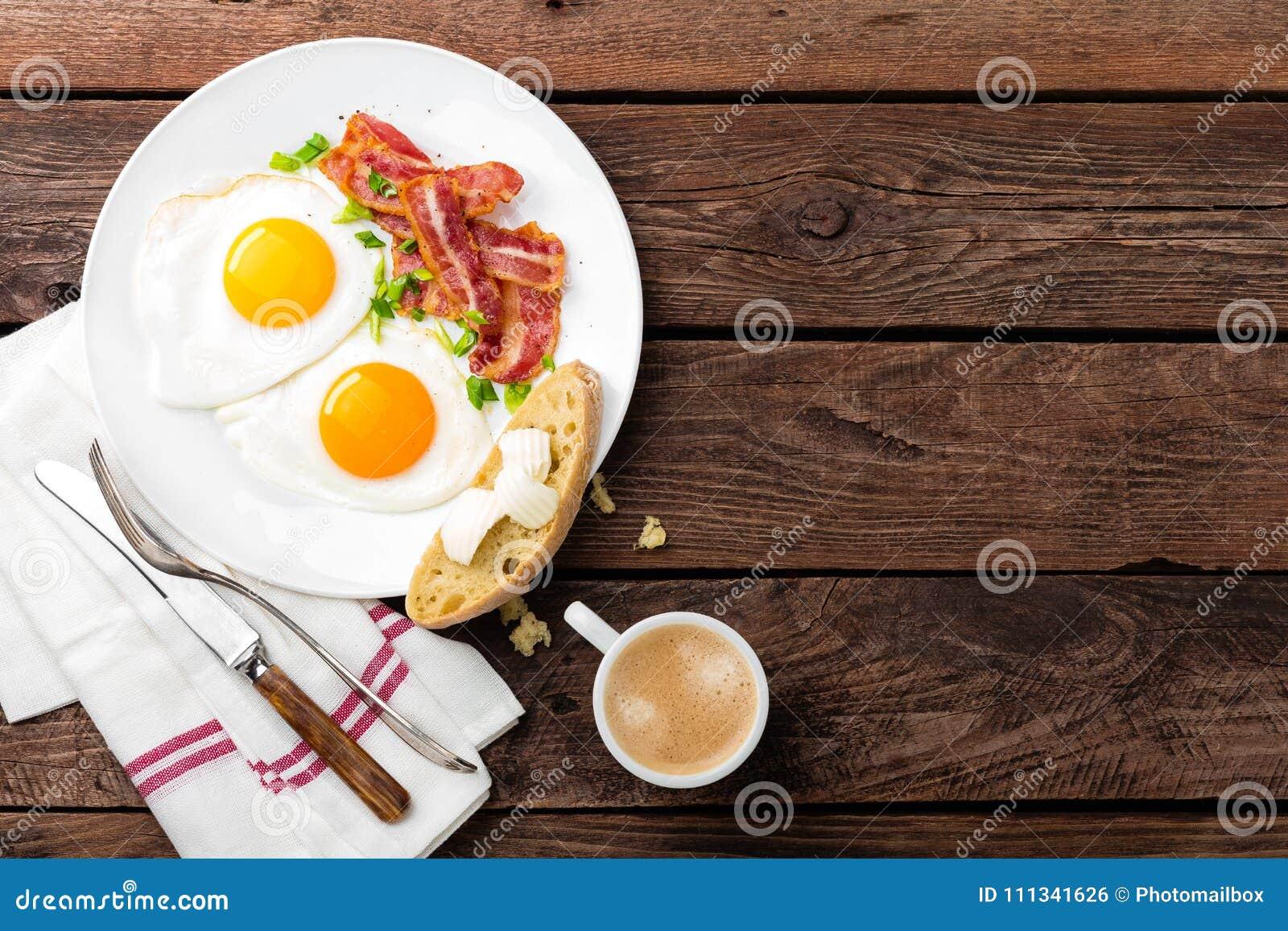 Gebraden eieren, bacon en Italiaans ciabattabrood op witte plaat Kop van koffie Ontbijt hoogste mening Houten achtergrond