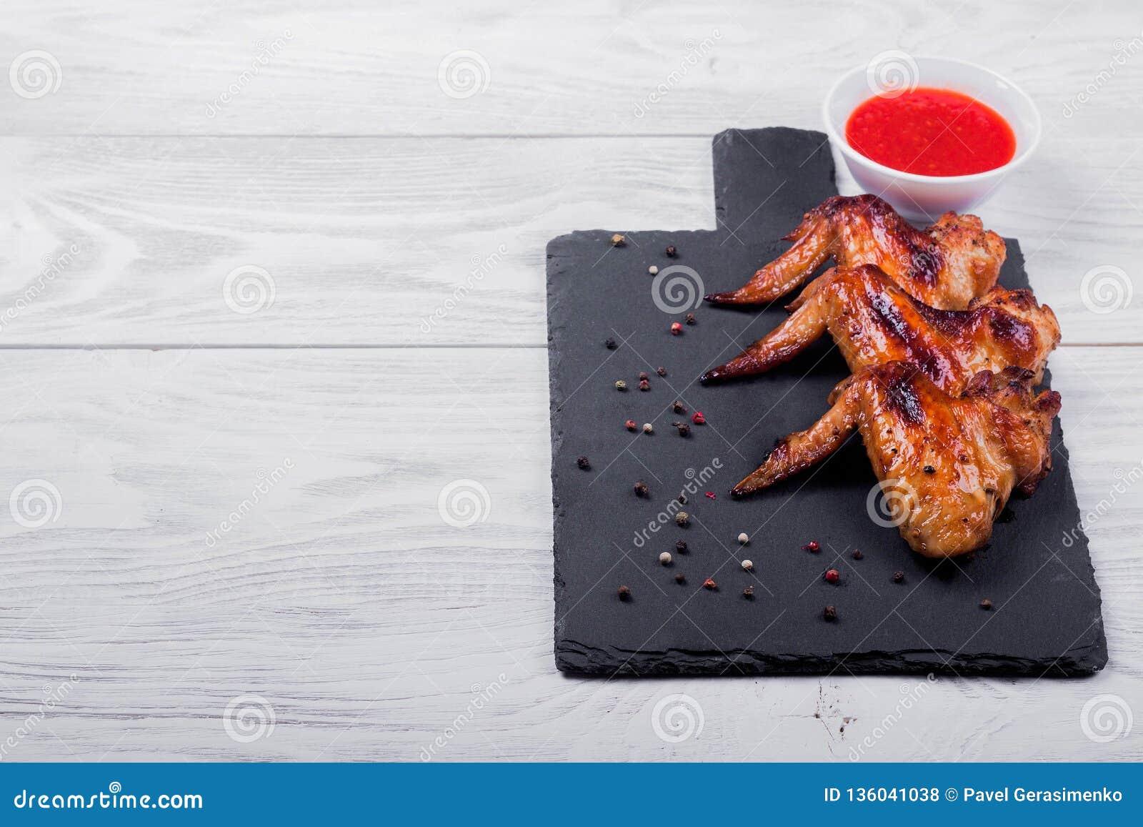 Gebraden kippenvleugels op een zwarte plaat met saus, houten achtergrond
