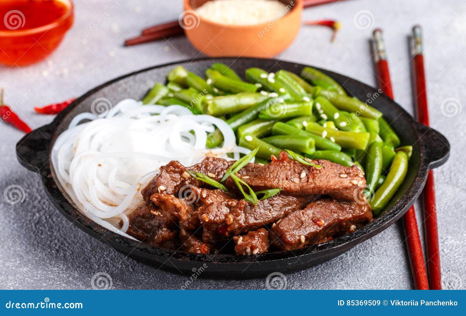 Gebraden kruidig rundvlees met sesamzaden, slabonen en rijstnoedels