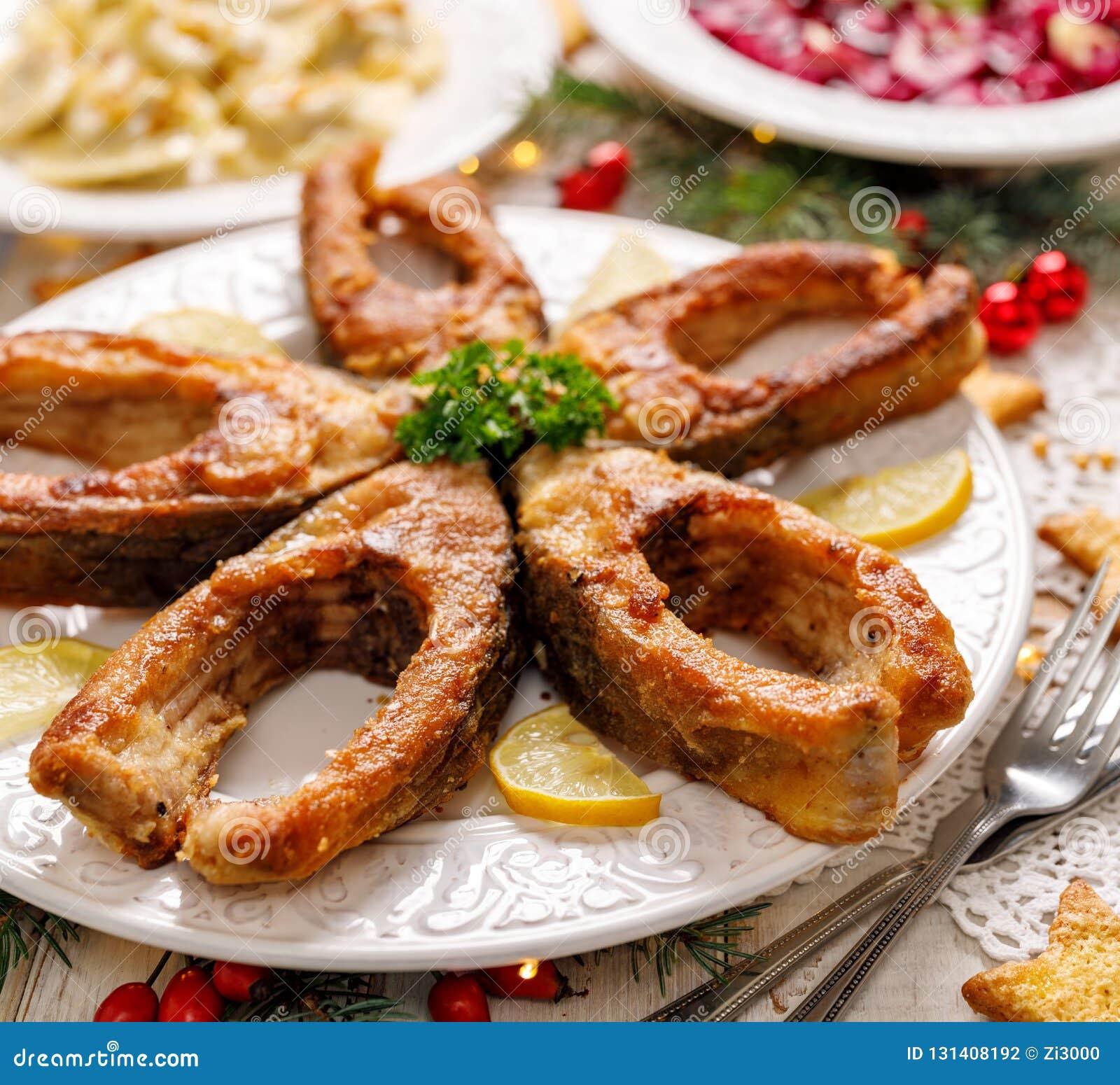 Gebratene Karpfenfischscheiben auf einer weißen Platte, Abschluss oben Traditioneller Weihnachtsabendsteller