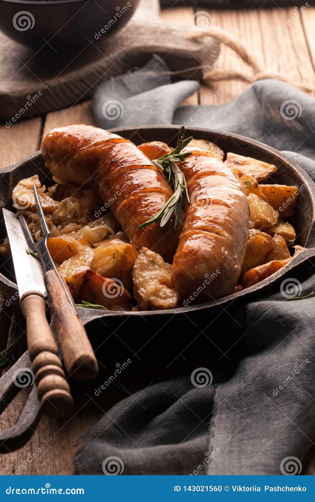 Gebratene Kartoffeln und gegrillte Würste in der Wanne mit Gabel, Messer, grauer Serviette und hackendem Brett