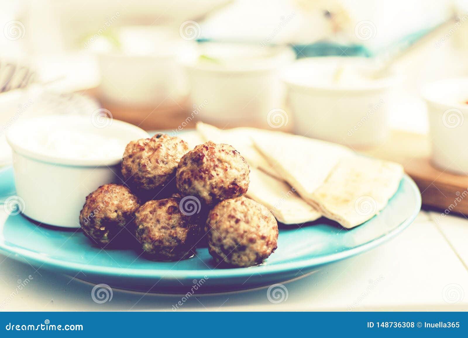 Gebratenes Hackfleisch mit So?e und Tortillas, traditionelles griechisches Mittagessen auf einer blauen Platte in einem Restauran