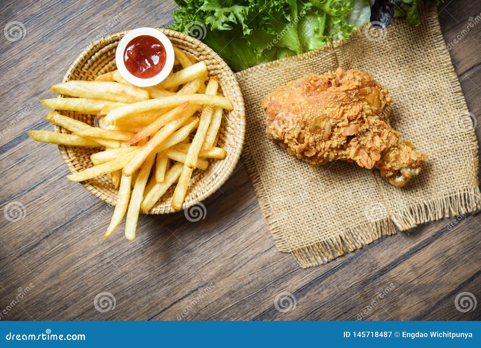 Gebratenes Huhn knusperig und Salatkopfsalatsack mit Pommes-Friteskorbketschup auf hölzernem Speisetischhintergrund