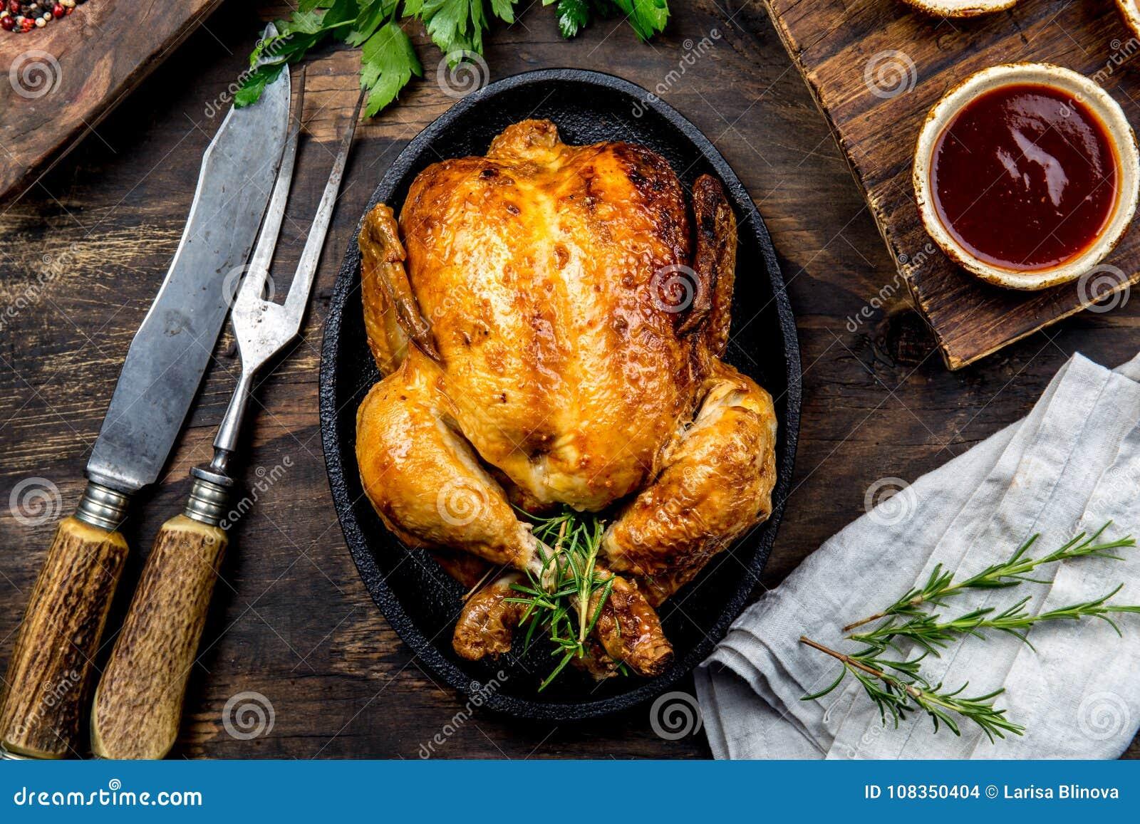 Gebratenes Huhn mit Rosmarin diente auf Schwarzblech mit Soßen auf Holztisch, Draufsicht