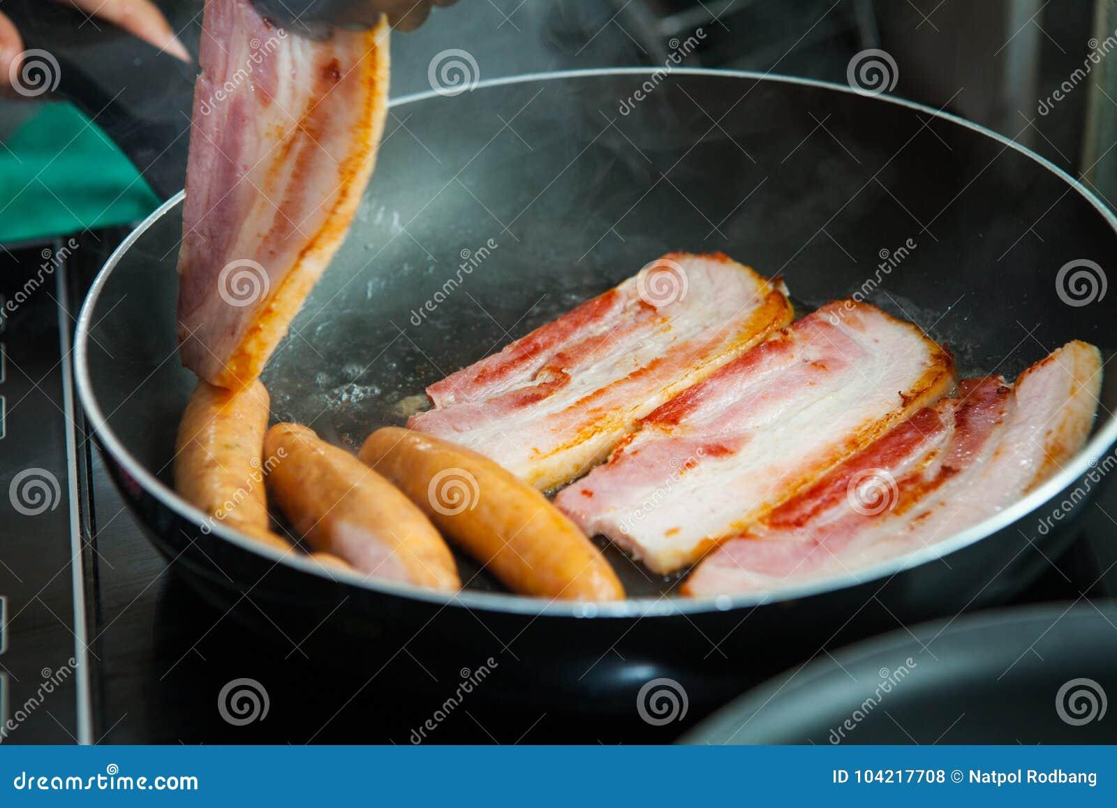 Gebratenes Schweinefleisch und Wurst, die in der Wanne kocht