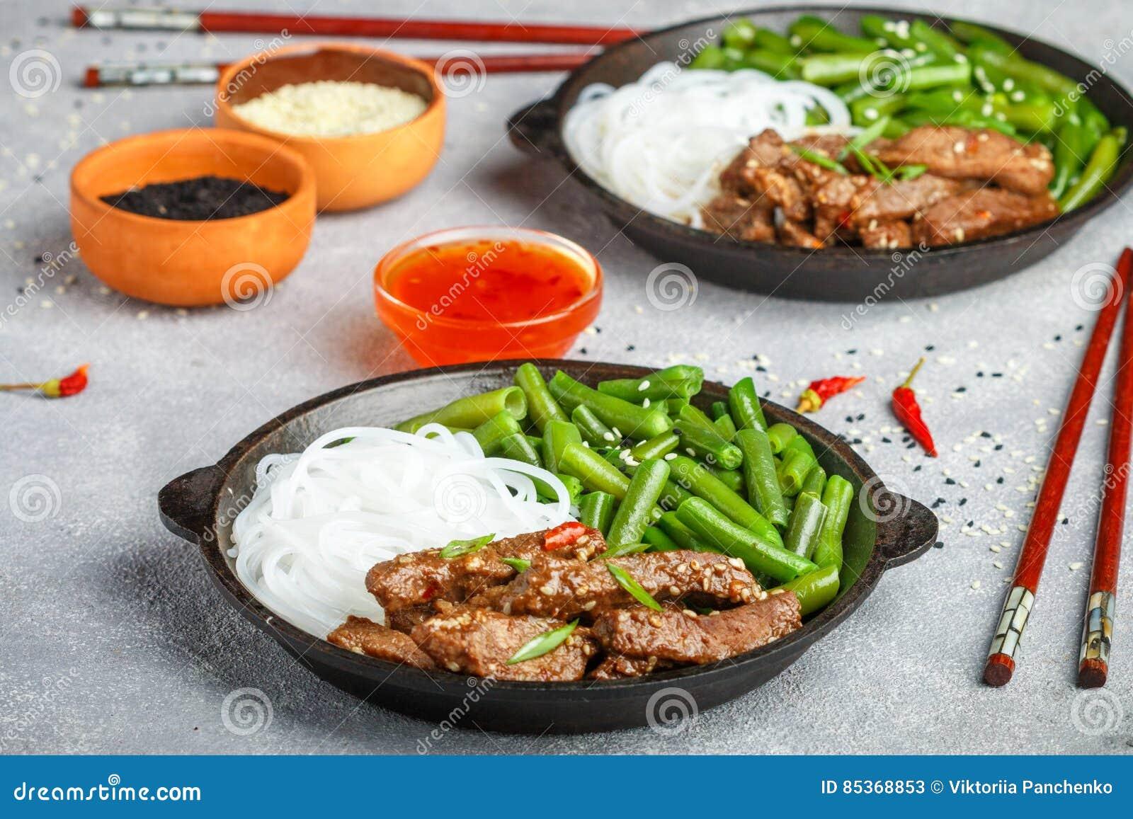Gebratenes würziges Rindfleisch mit Samen des indischen Sesams, grünen Bohnen und Reisnudeln