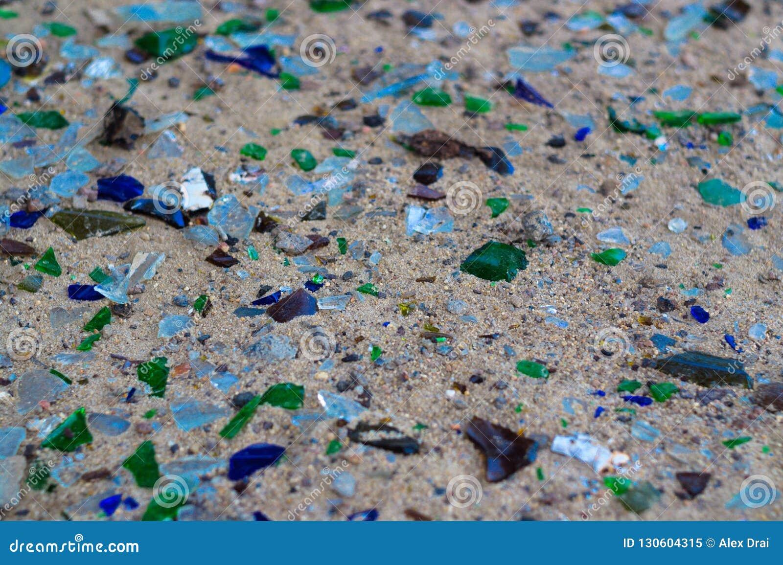Gebroken glasflessen op wit zand De flessen is groene en blauwe kleur Afval op het zand Ecologisch probleem