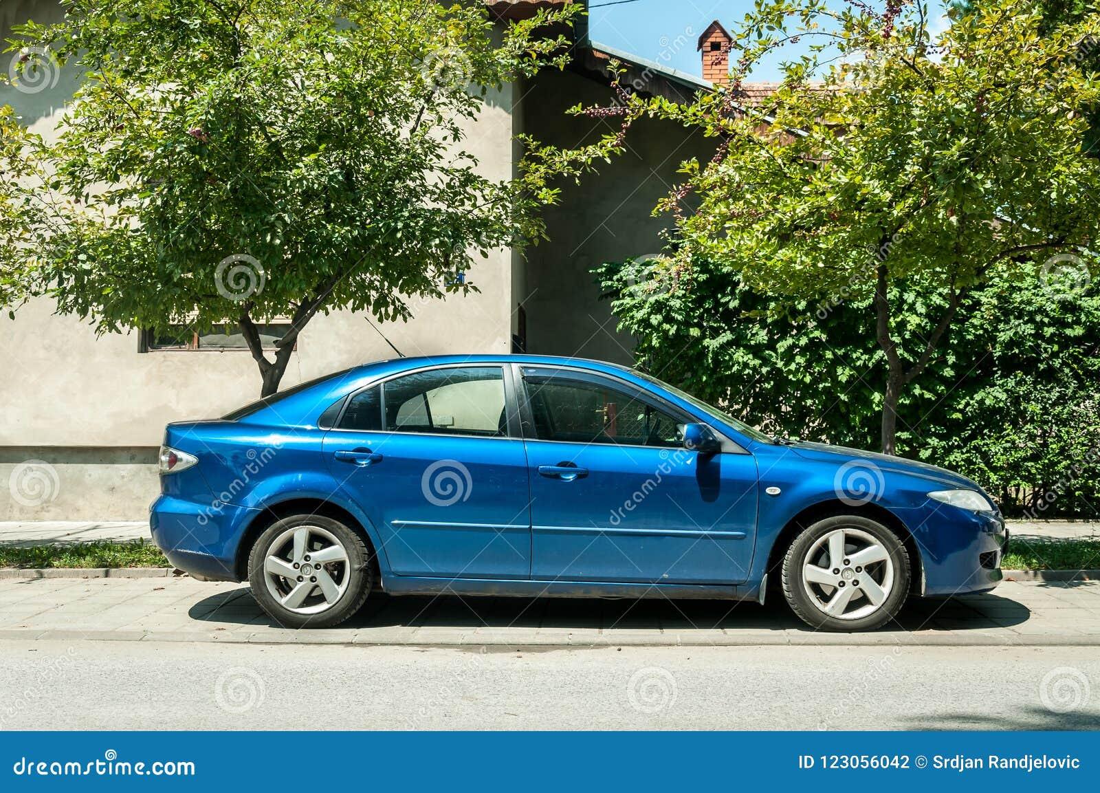 Gebruikt blauw die Mazda 6 auto op de straat in de stad wordt geparkeerd