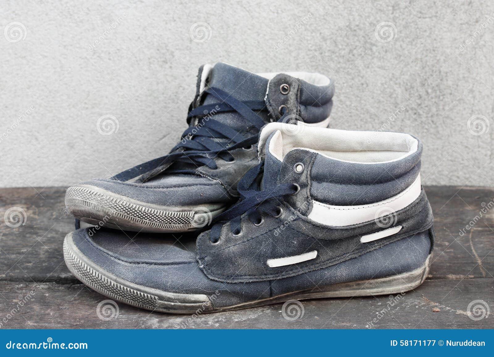 Gebruikte Houten Vloer : Gebruikte oude tennisschoenen op de houten vloer stock afbeelding