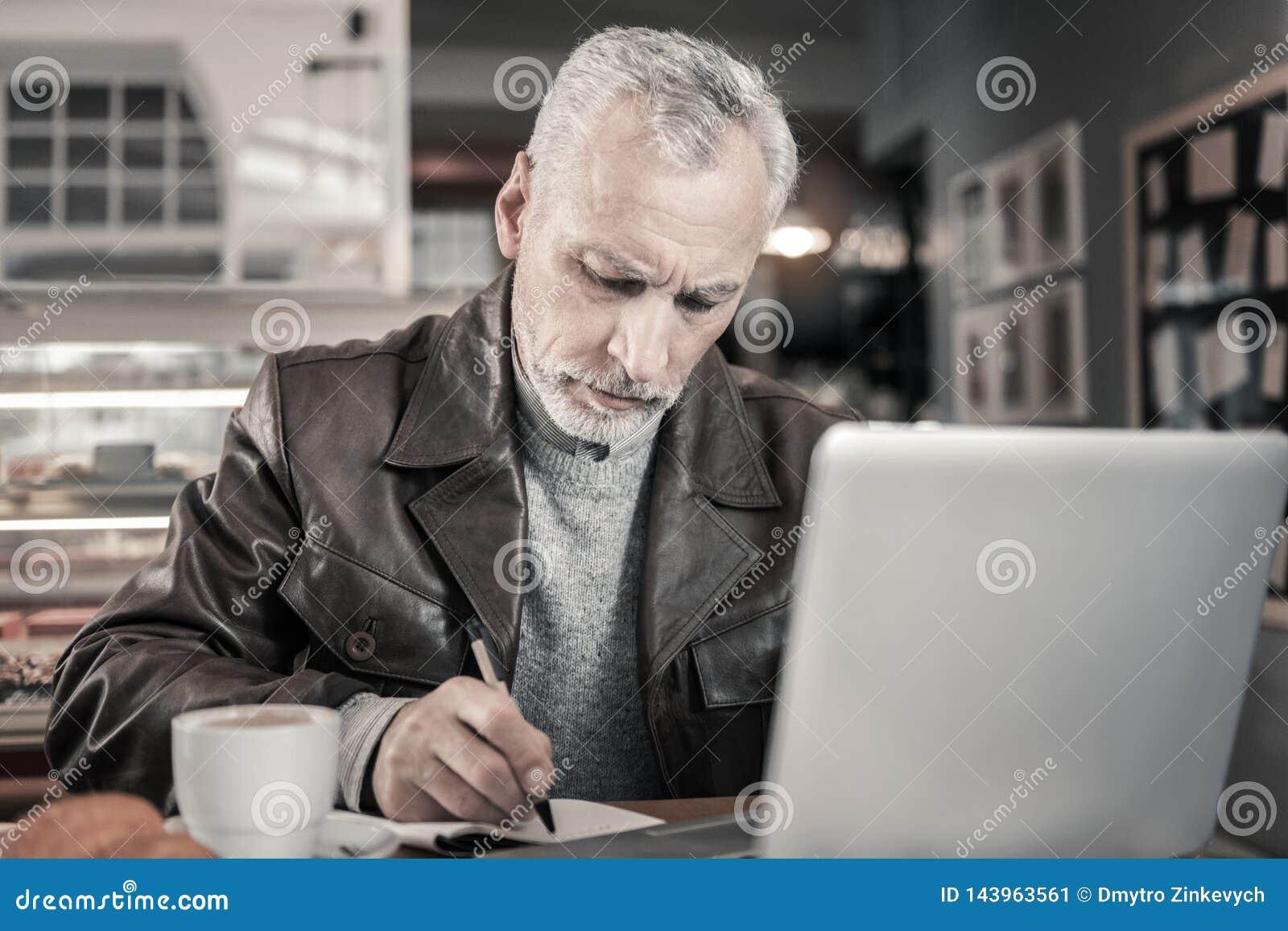 Geconcentreerd grijs-haired mannetje die nota s in voorbeeldenboek maken