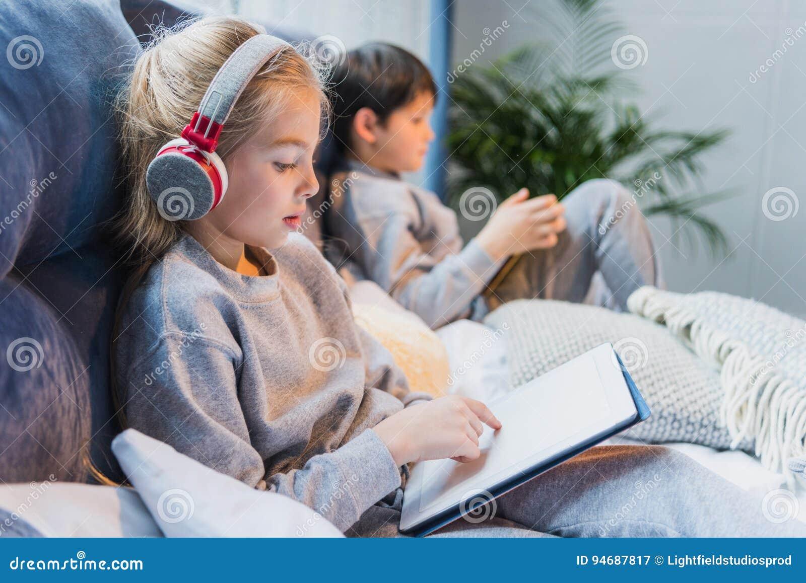 Geconcentreerd meisje in hoofdtelefoons en weinig jongen die digitale tabletten gebruiken