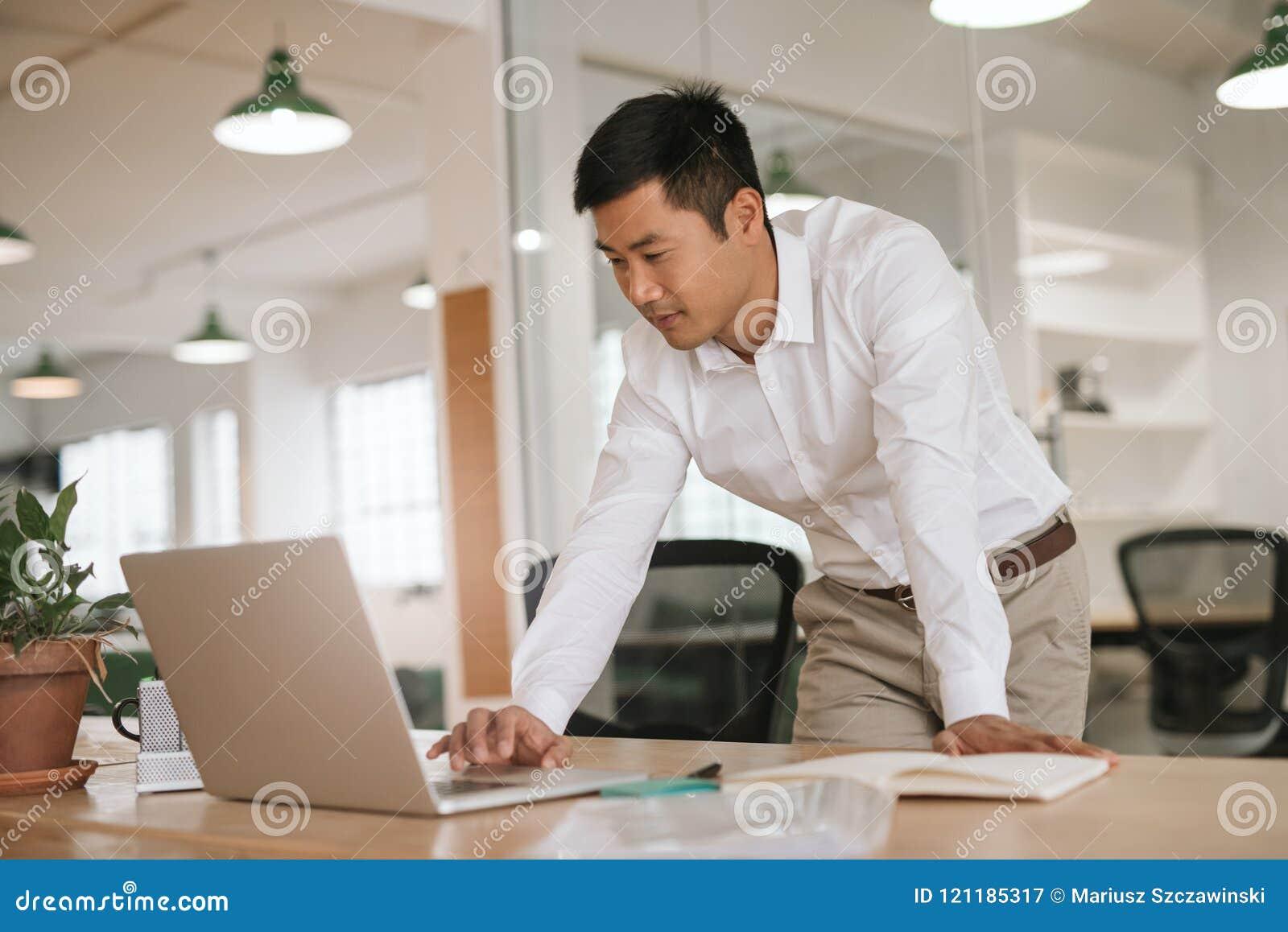 Geconcentreerde jonge Aziatische zakenman die online bij zijn bureau werken