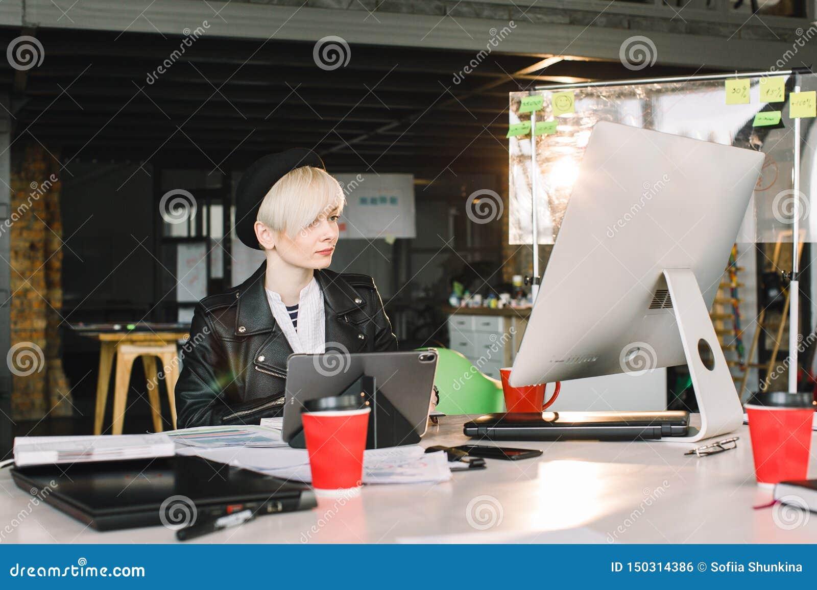 Geconcentreerde jonge mooie blonde onderneemster die in vrijetijdskleding aan PC en tablet in helder zolder modern bureau werken