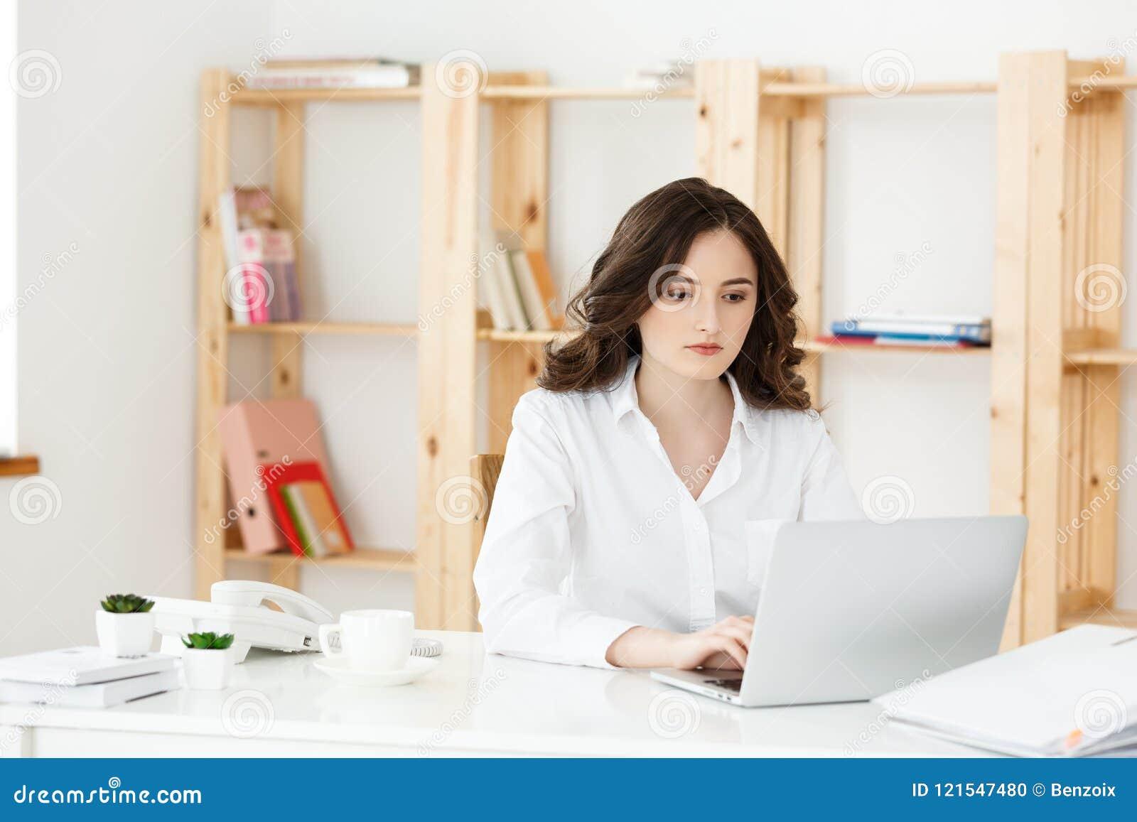 Geconcentreerde jonge mooie onderneemster die aan laptop en document in helder modern bureau werken