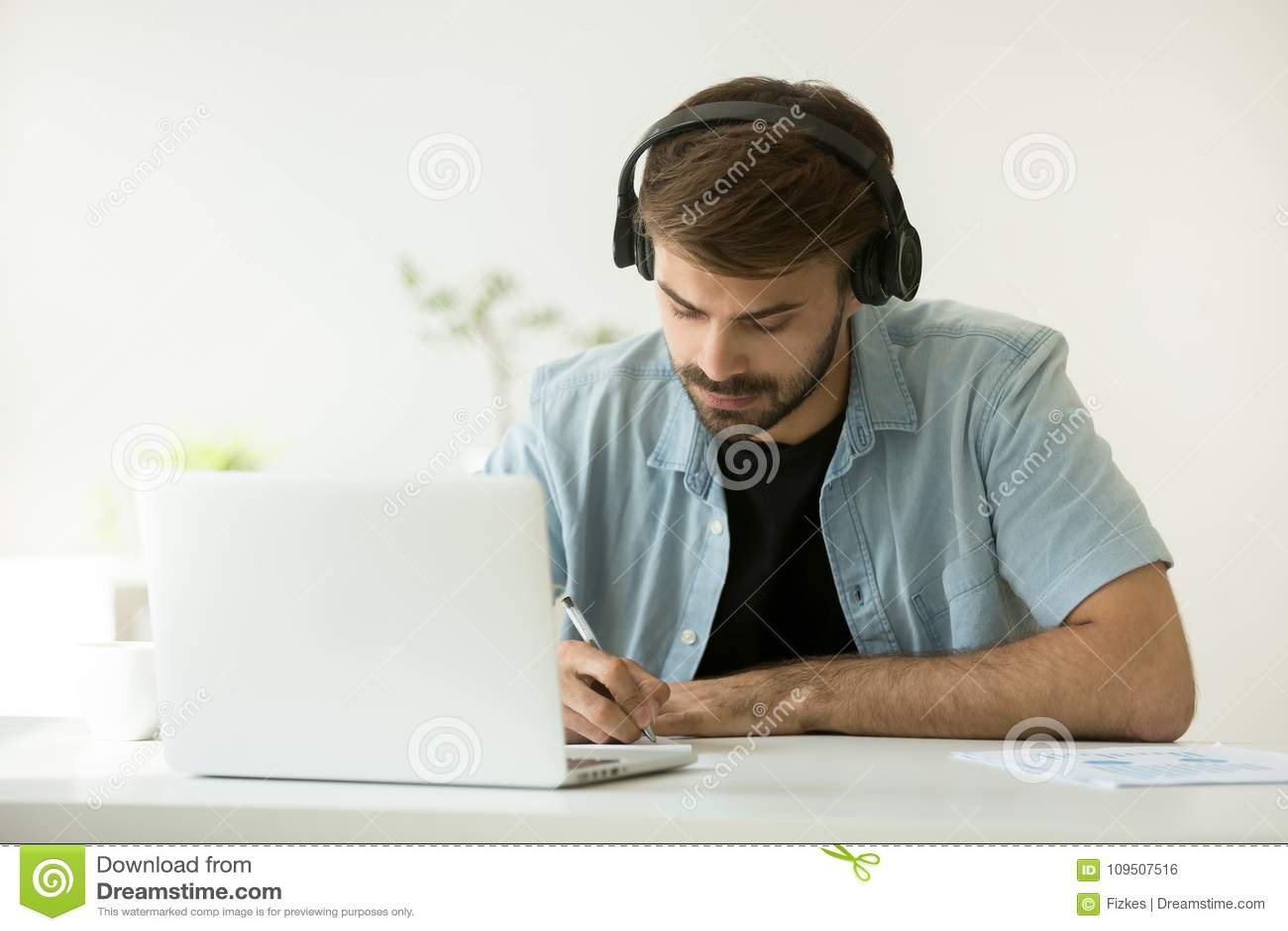 Geconcentreerde mens die hoofdtelefoons dragen die nota s schrijven die online verstand leren