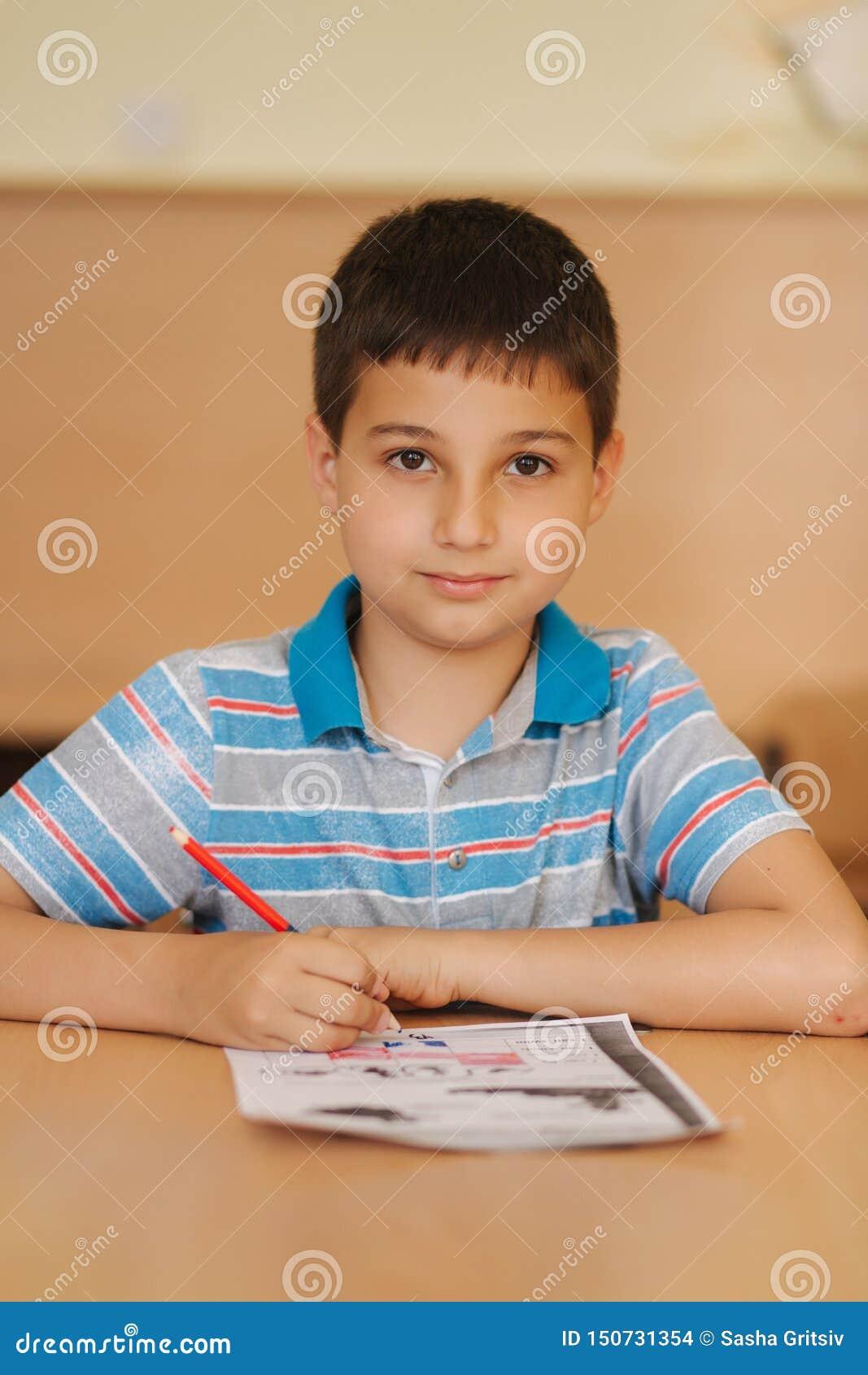 Geconcentreerde schooljongenzitting bij bureau en het schrijven in oefenboek