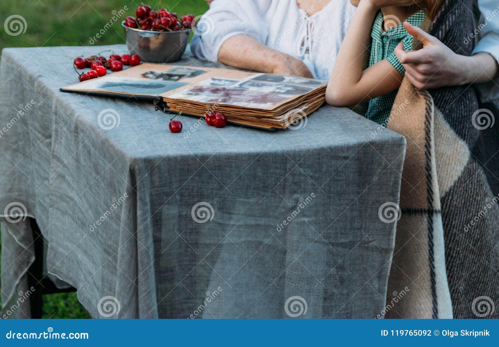 Gedächtnisse der älteren Personen Besuchsgroßmutter Großmutter mit ihren Enkelkindern, die in einem Stuhl im Garten sitzen und ei