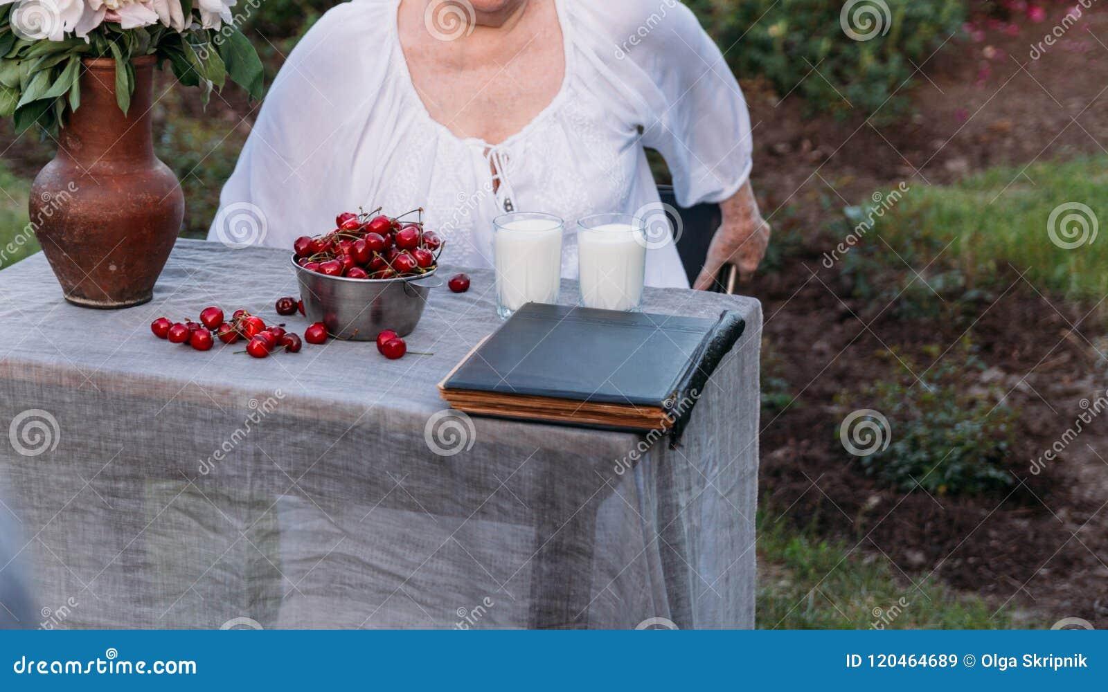 Gedächtnisse der älteren Personen Großmutter, die in einem Stuhl im Garten sitzt