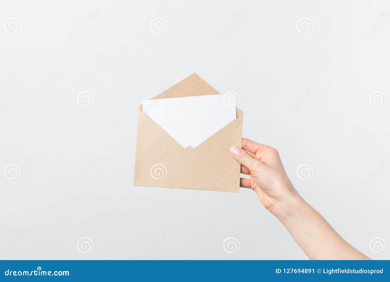 Gedeeltelijke mening van de envelop van kraftpapier van de vrouwenholding met lege kaart in hand op wit