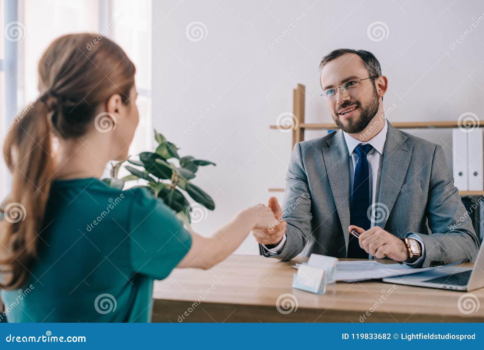 Gedeeltelijke mening van zakenman en cliënt het schudden handen tijdens vergadering