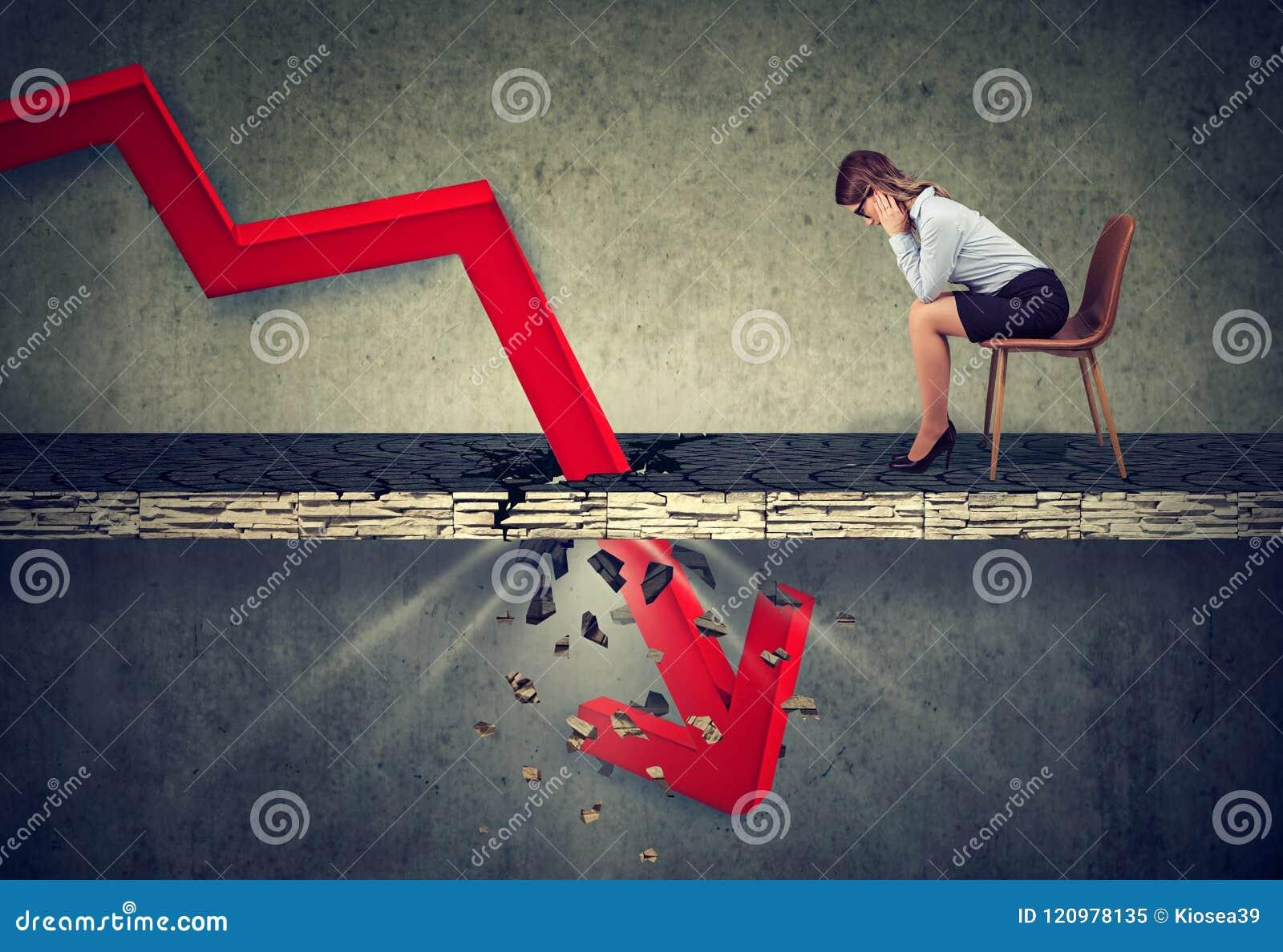 Gedeprimeerde bedrijfsvrouw die neer de dalende rode pijl bekijken