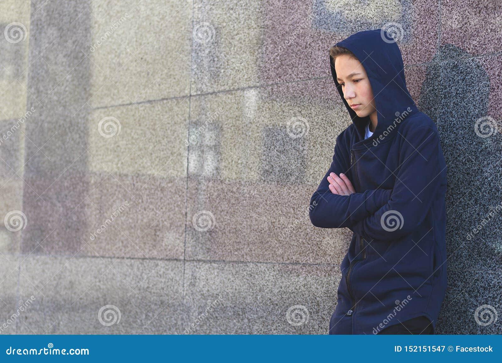Gedeprimeerde droevige tiener op een donkere achtergrond, tienerprobleemconcept