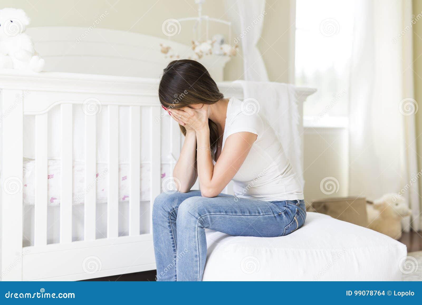 Gedeprimeerde jonge vrouw in babyruimte