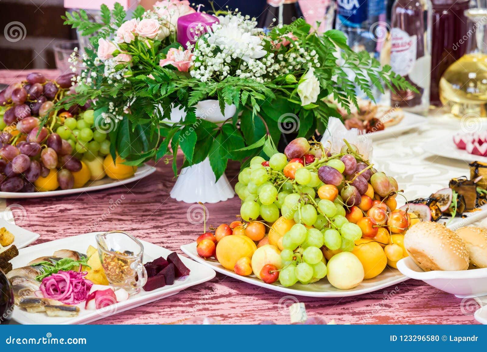 Gediende lijst bij het Banket Vruchten, snacks, delicatessen en bloemen in het restaurant Plechtig gebeurtenis of huwelijk