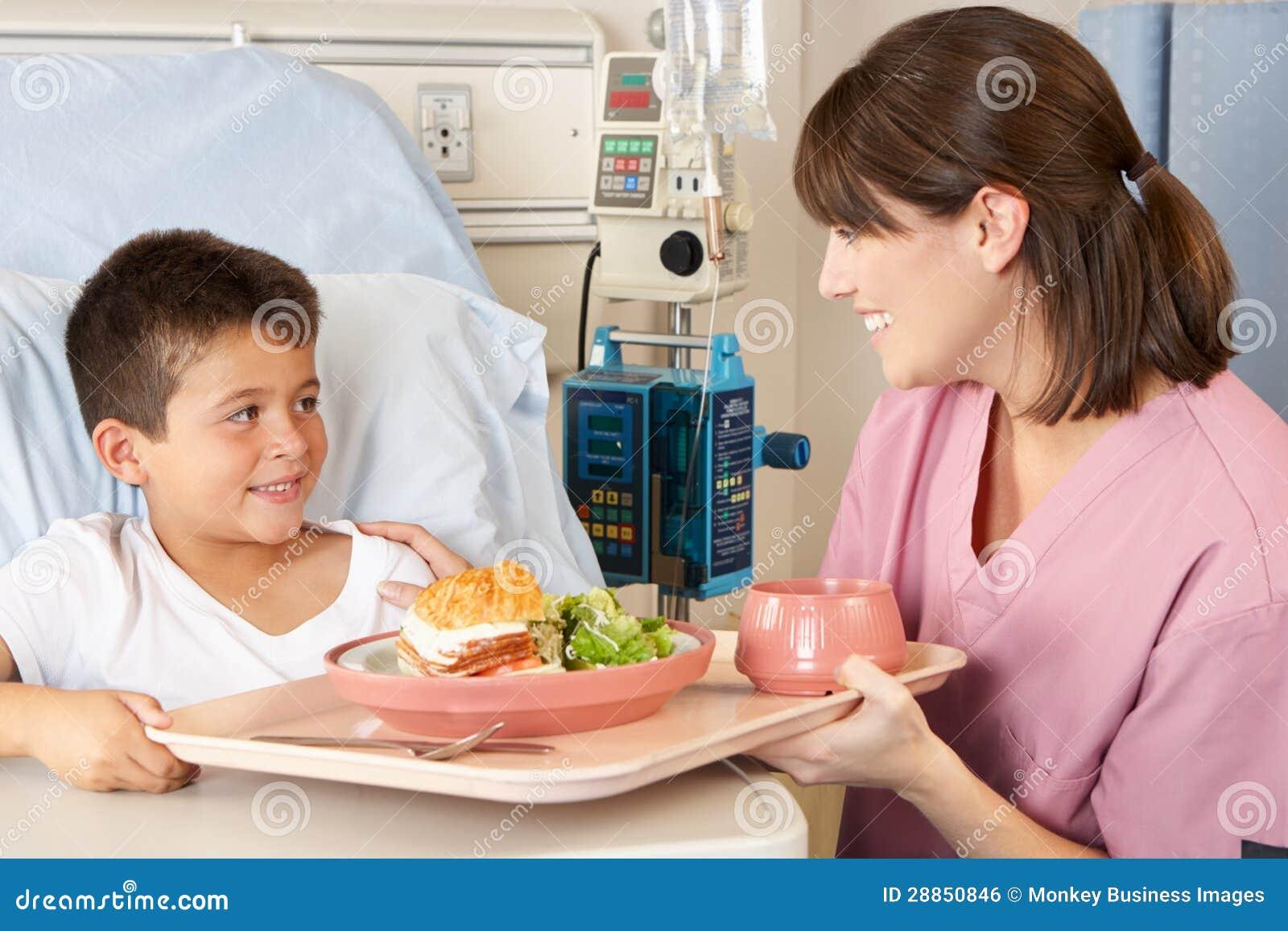 Geduldige Maaltijd van het Kind van de verpleegster de Dienende in het Bed van het Ziekenhuis