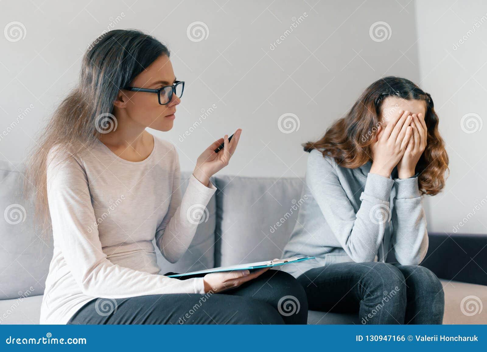 Geduldiges Mädchen des Jugendlichen, das mit Berufspsychotherapeuten im Büro spricht Mädchen ist, sie bedeckte Gesicht mit ihren