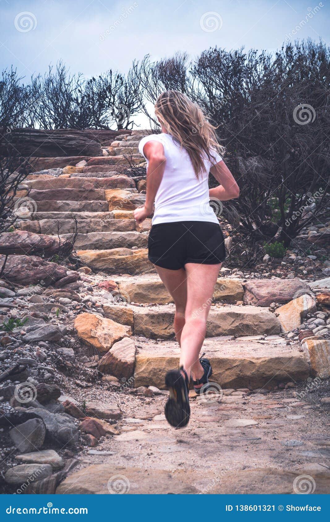 Geeignete aktive Frau, die oben Treppe Landschaft in der im Freien laufen lässt