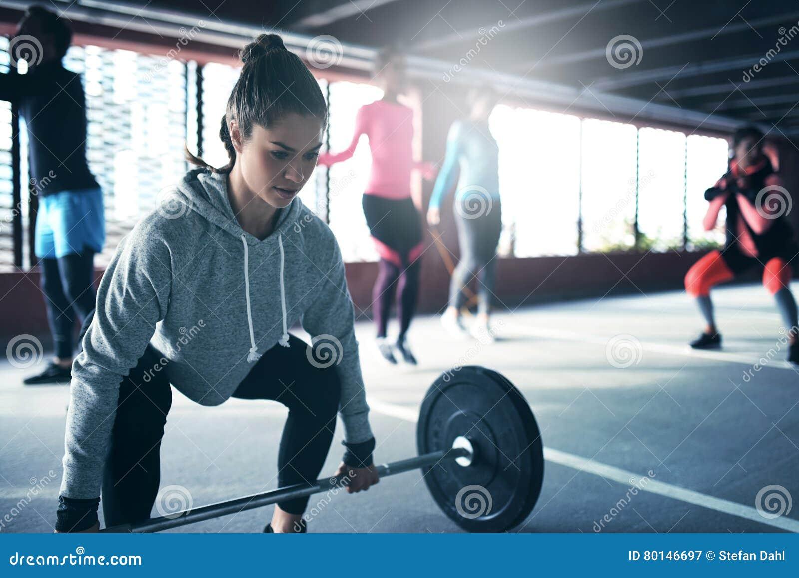 Geeignete gesunde Frau, die einen Gewicht Barbell anhebt