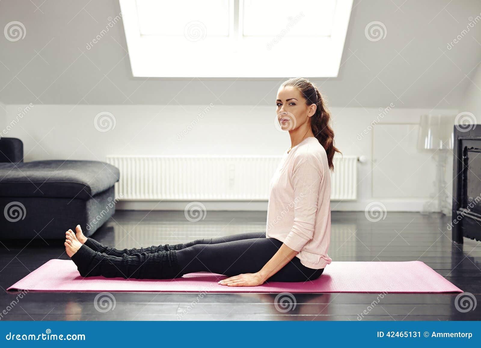 Geeignete junge Frau, die auf Übungsmatte - zuhause sitzt