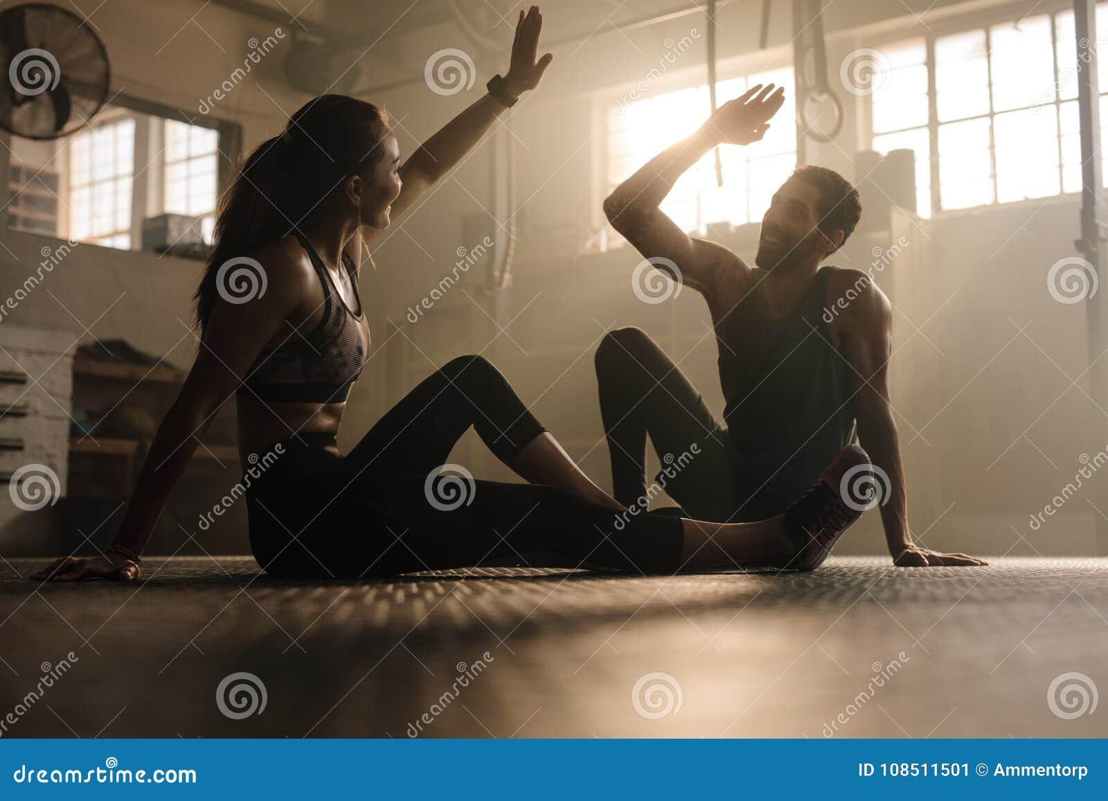 Geeignete Paare hohe fünf nach Training im Fitnessstudio
