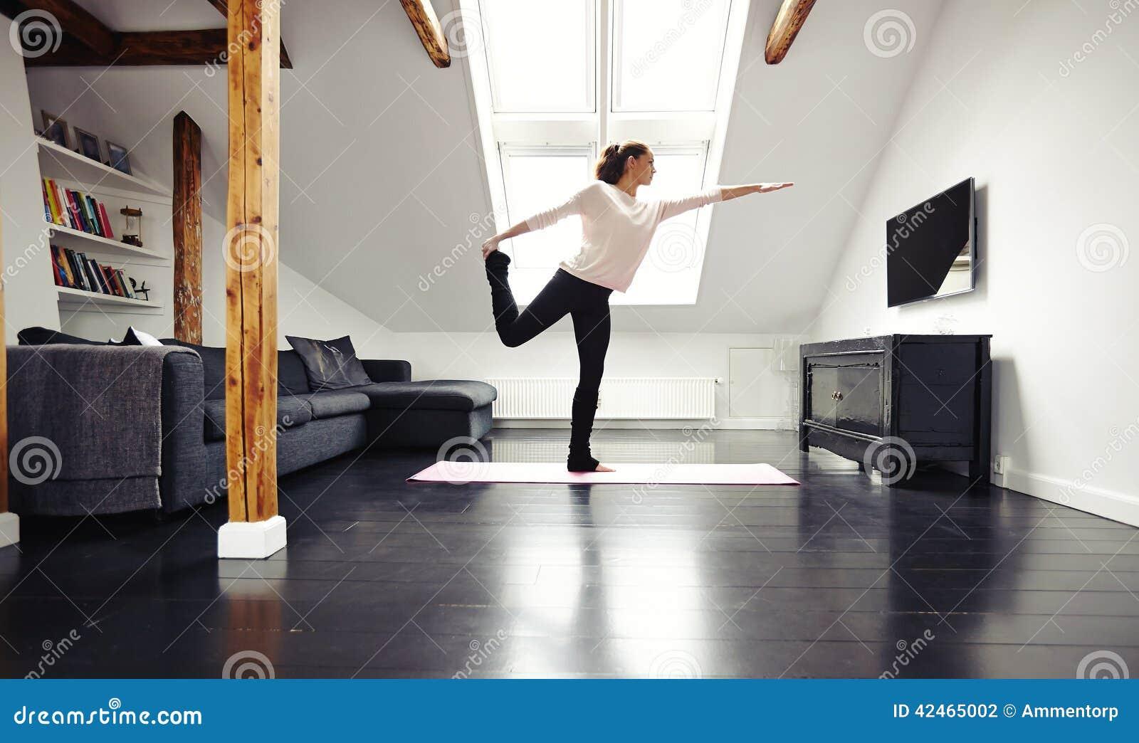 Geeignete Yoga junger Dame übende zu Hause - Kriegershaltung