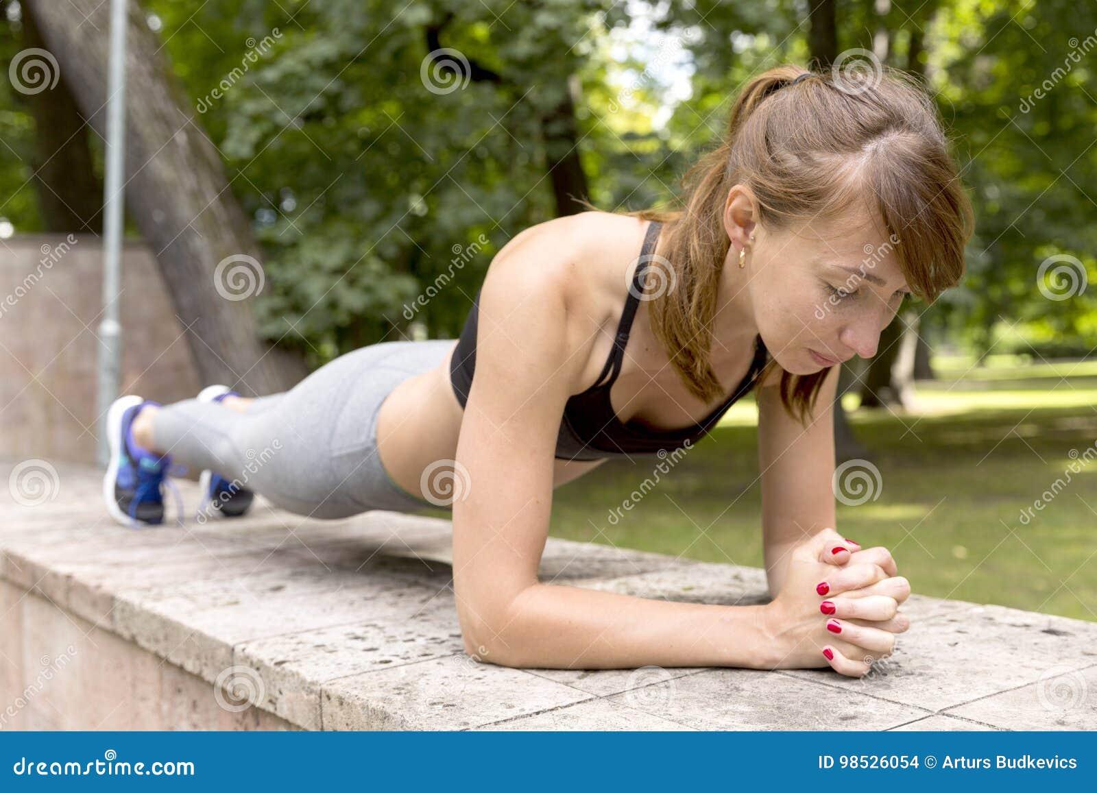 Geeignetes Mädchen, welches die Plankenübung im Freien am warmen Sommertag des Parks tut Konzept von Ausdauer und von Motivation