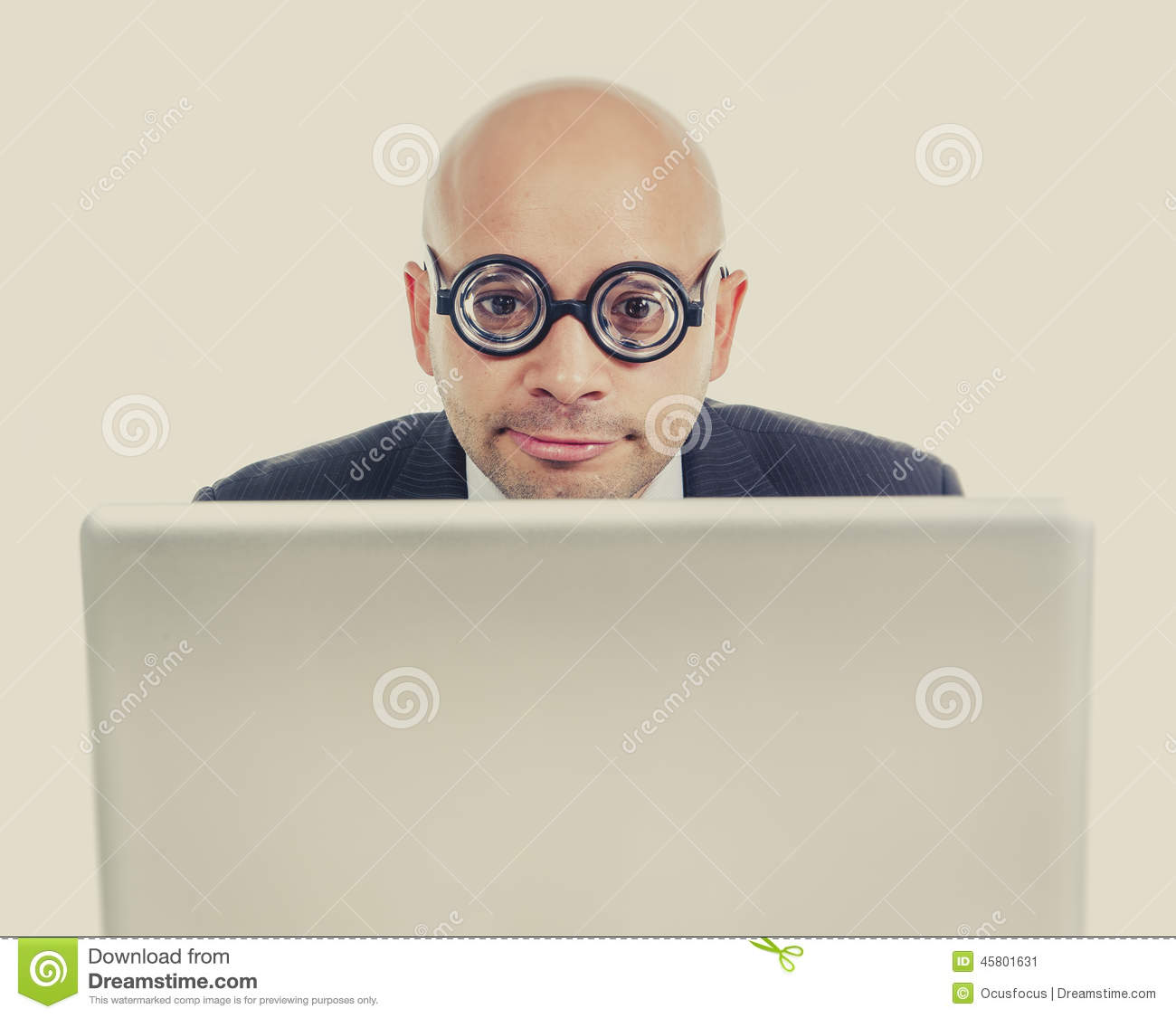 Geek and freak bald head businessman with computer laptop wearing thick glasses looking nerd