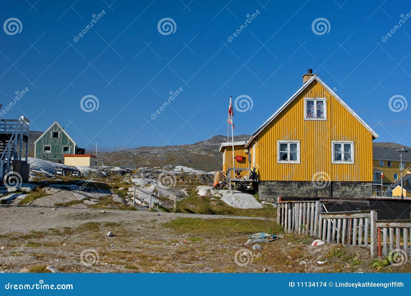 Geel huis in Groenland met vlag en omheining