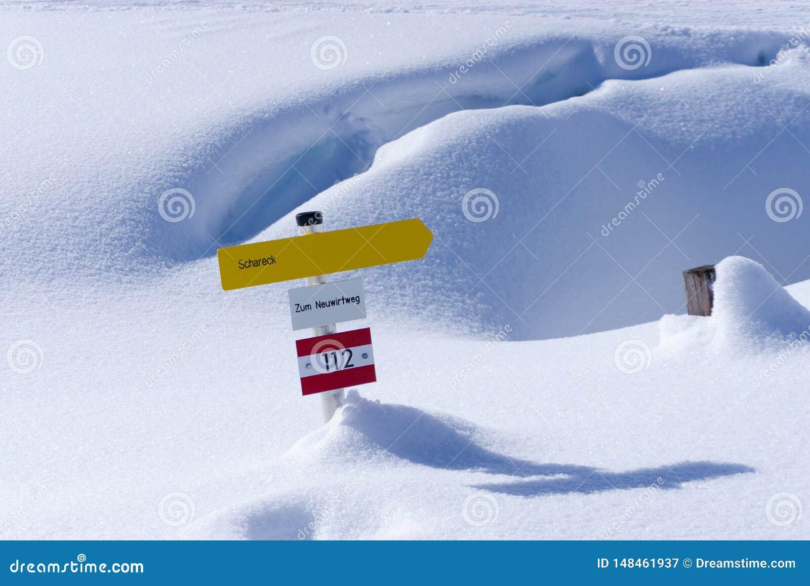Geel wandelingsteken in de sneeuw van Oostenrijk