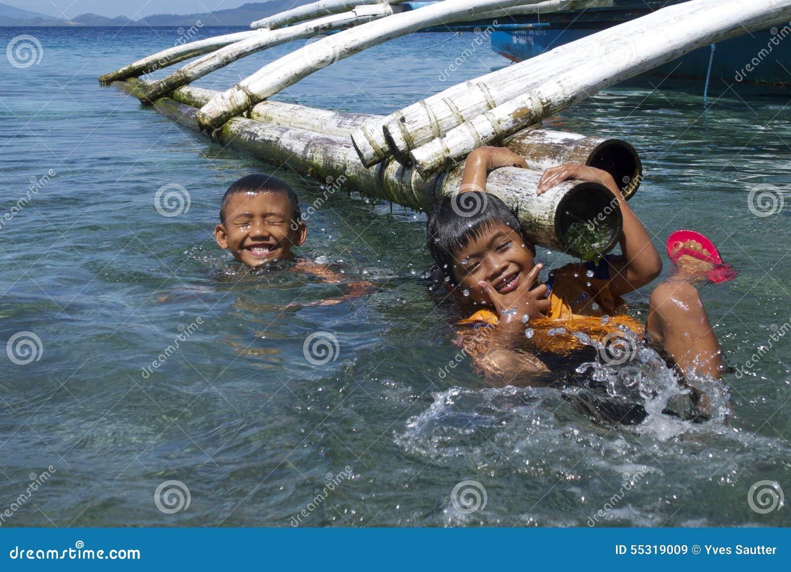 Geen videospelletjes hier Filipijnse jonge geitjes die pret hebben die in Leyte, Filippijnen, Tropisch Azië zwemmen