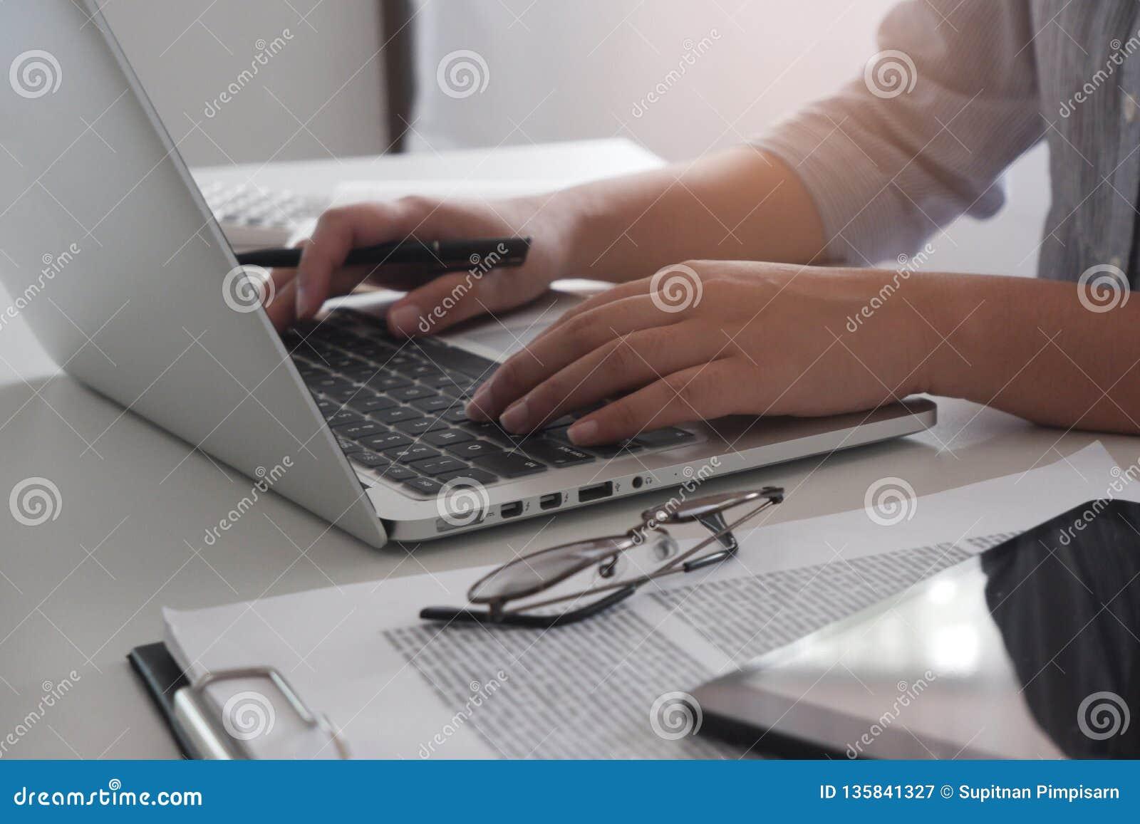 Geerntetes Bild der Berufsgeschäftsfrau arbeitend in ihrem Büro über den jungen weiblichen Manager des Laptops, der Gerät des tra