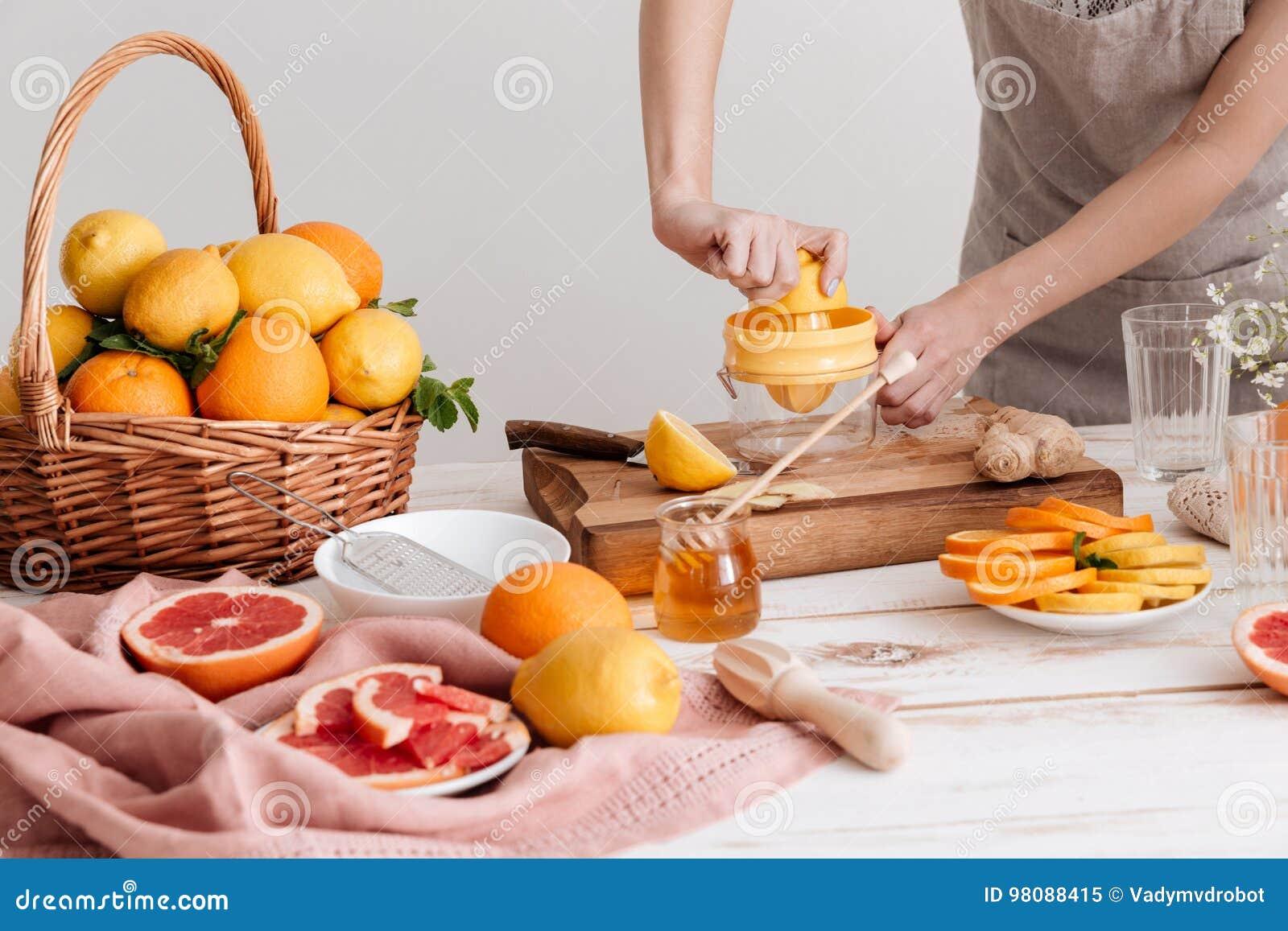 Geerntetes Bild der Frau drückt heraus Saft von Zitrusfrüchte zusammen