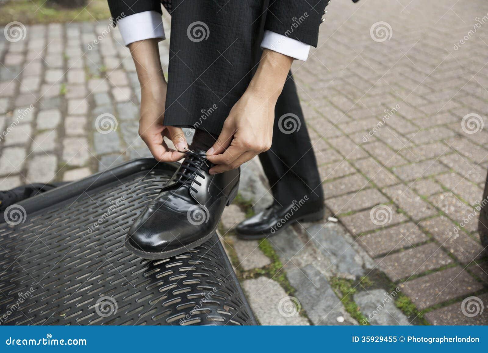 Geerntetes Bild des Geschäftsmannes seinen Schuh auf Bank binden