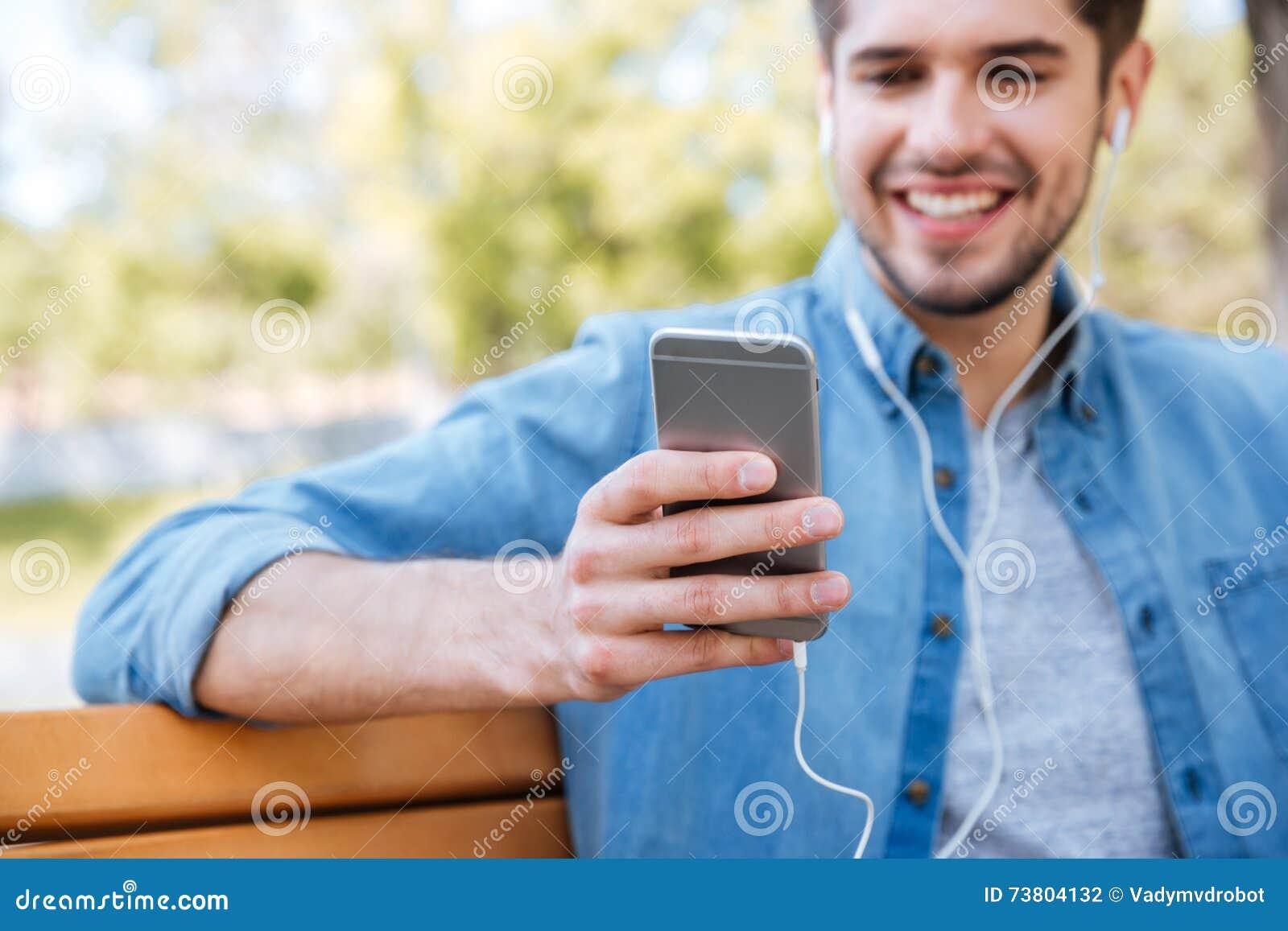 Geerntetes Bild eines jungen Mannes, der mit Handy sitzt