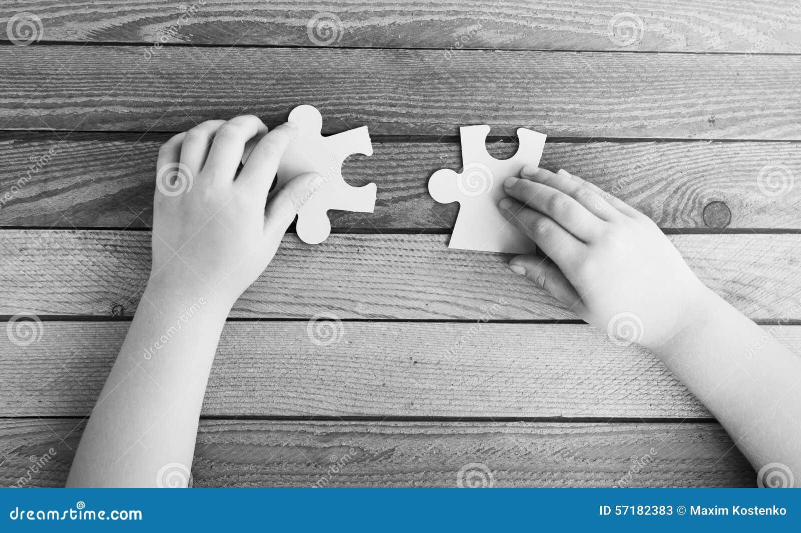 Geerntetes Bild von den Händen, die zwei Puzzlespielstücke anschließen