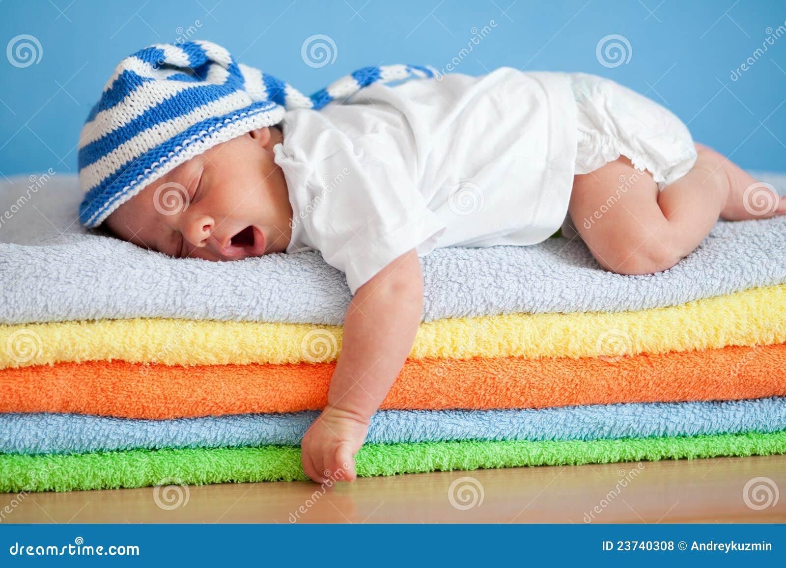 Geeuwende slaapbaby op kleurrijke handdoekenstapel