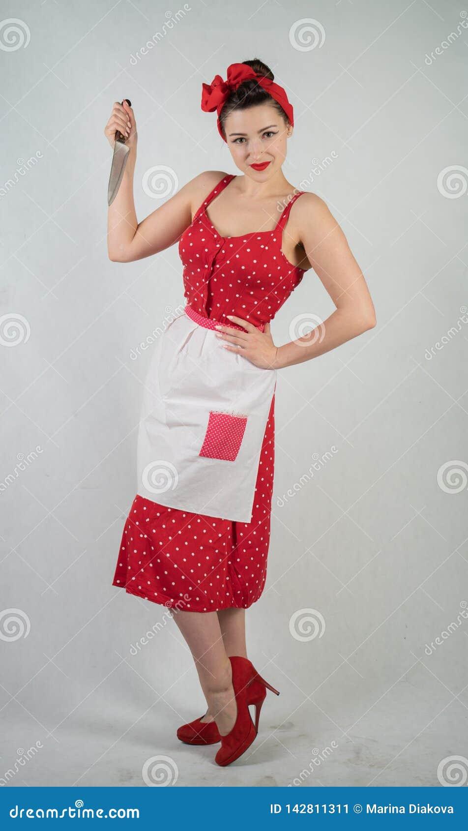 Gefährlicher Stift herauf Mädchenhausfrau im roten Weinlesetupfenkleid steht mit einem Messer der großen Küche in ihren Händen un