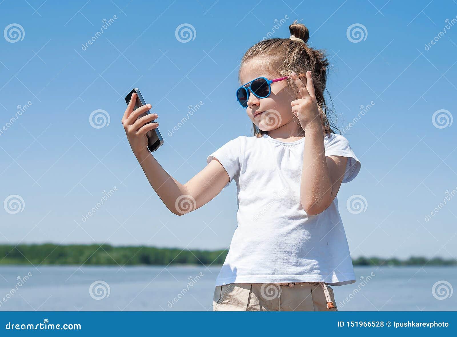 Gefühle, Ausdrücke und Leutekonzept - glückliches Kleinkind oder Jugendliche, die selfie mit Smartphone über blauem Himmel nehmen