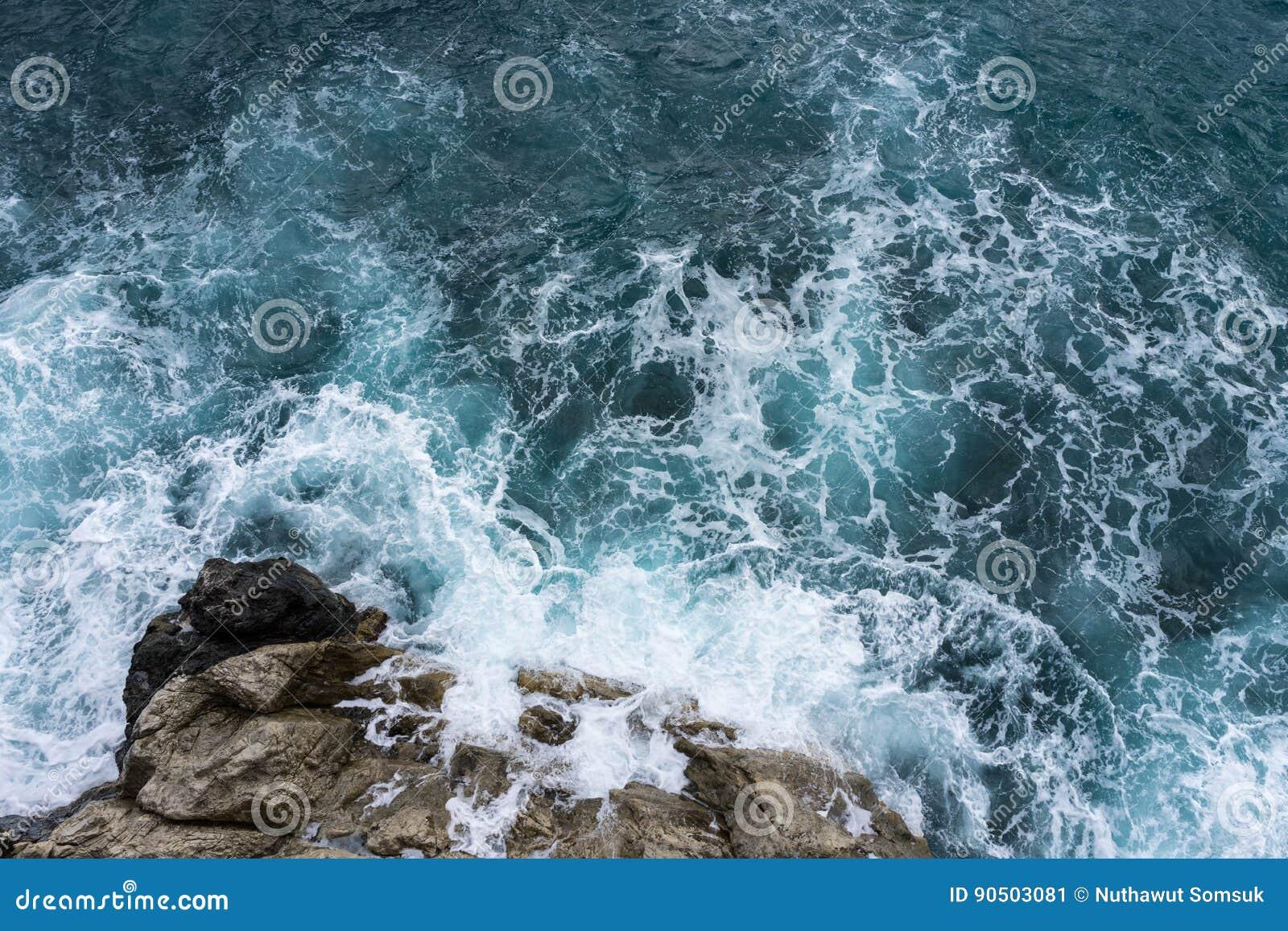 Gefahrenseewelle, die vorher auf Felsenküste mit Spray und Schaum zusammenstößt